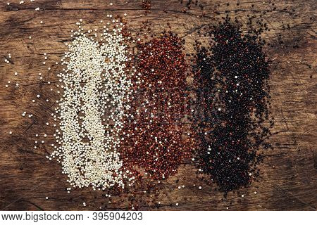 Black, White And Red Quinoa In Spoons, Raw Quinoa Groats Assorted, Wooden Rustic Kitchen Table, Top