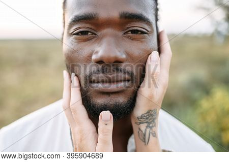 Close-up Picture Of The Face Of Handsome Black Guy, A White Female Palms Are Gently Touching His