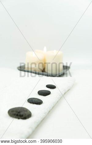 Gray Zen Pebble Hot Stones With Towel On Massage Table In Beauty Salon. Hot Stone Massage Setting. C