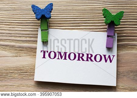 Tomorrow - Word On A White Sheet With Beautiful Clothespins On A Wooden Background. Info Concept