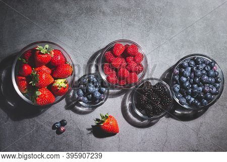 Assorted Berries In Glass Bowls On Dark Background Top View.