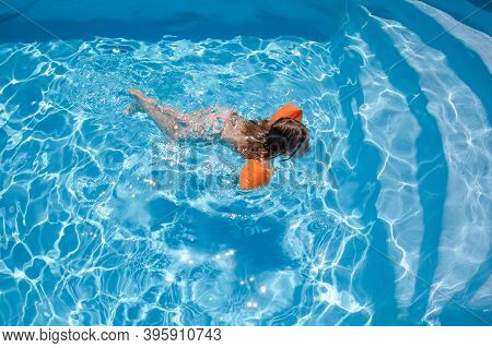 Child With Armbands Swimming In Pool Towards Stairs