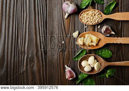 Flat Lay View At Wooden Spoons With Food Ingredients For Genovese Pesto Sauce On Kitchen Table