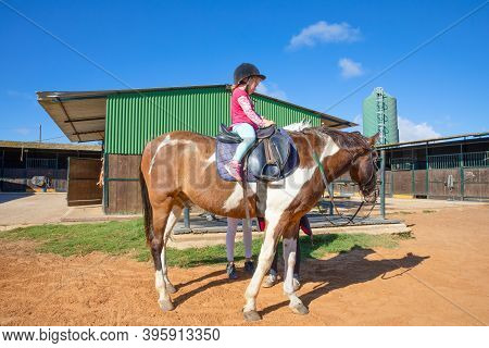 Side View Of Little Girl Sitting On A Horse In A Riding Center