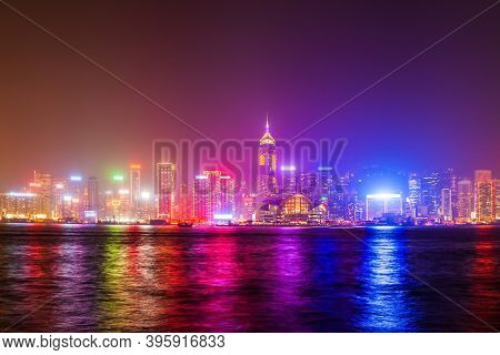 Hong Kong Island Skyline Viewed From The Victoria Harbour Waterfront At Night. Hong Kong Is A City A