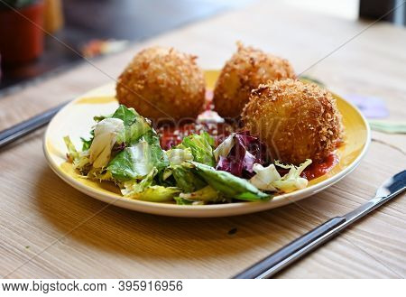 Homemade Fried Vegetarian Arancini With Some Fresh Lettuce Served With Tomato Sauce On The Wooden Ca