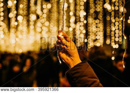 A Girl Holds A New Year Or Christmas Garland In Her Hands During The Holiday. Christmas Lights In Th