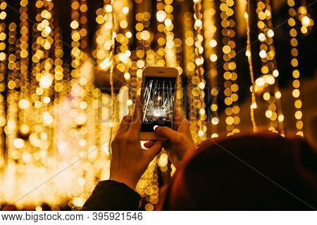 The Girl Takes Pictures Of Christmas Or New Years Lights On The Phone.