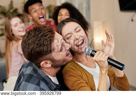 Sing Together. Young Excited Couple Or Friends Holding Microphone And Singing Together While Playing
