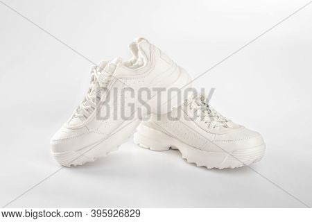 White Sneakers On White Background. Pair Of Trendy Womens Sneakers On White. Sports Shoes For Cold W