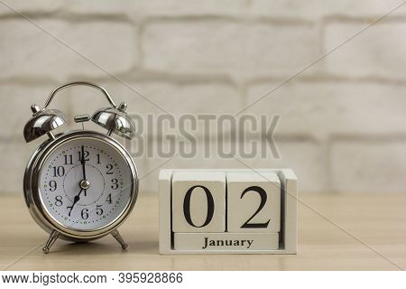 January 2 On A Wooden Calendar Next To The Alarm Clock.one Day In January.winter Day.copy Of The Spa