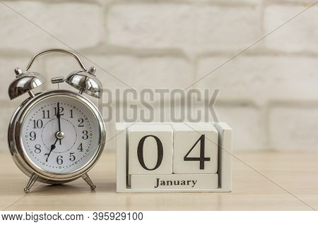 January 4 On A Wooden Calendar Next To The Alarm Clock.one Day In January.winter Day.copy Of The Spa