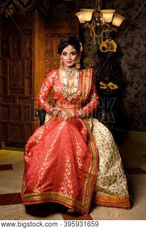 Magnificent Young Indian Bride In Luxurious Dress And Precious Jewellery Is Sitting In A Chair In A