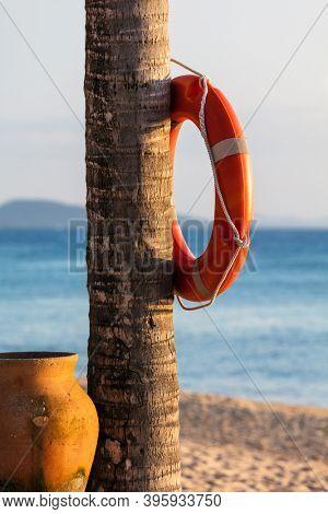 orange lifebuoy ring on a tropical beach