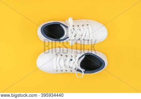 White Sports Shoes, Sneakers With Shoelaces On A Yellow Background. Sport Lifestyle Concept Top View