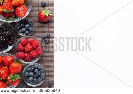 Berries In Glass Bowls On A Wooden Tablecloth On White Background With Copy Space . Top View.