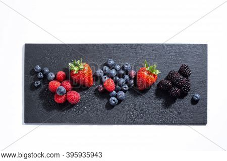 Fresh Berries On A Slate Plate On White Background. Top View.