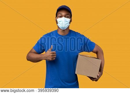 Express Delivery. Black Courier Man In Medical Mask, Blue Uniform And Cap Holding Box And Showing Th