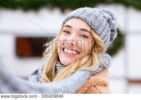 Closeup Portrait Of Beautiful Young Woman Posing Outdoors On Winter Day, Wearing Woolen Hat And Scar