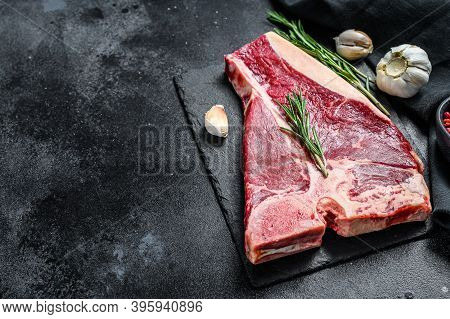 Raw Fresh Meat T-bone Steak With , Garlic And Rosemary. Organic T Bone Beef. Black Background. Top V
