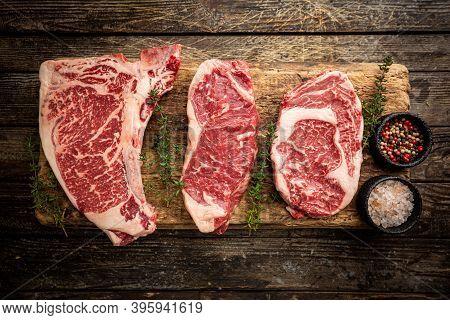 Variety Of Fresh Raw Black Angus Prime Meat Steaks T-bone, New York, Ribeye And Seasoning On Wooden