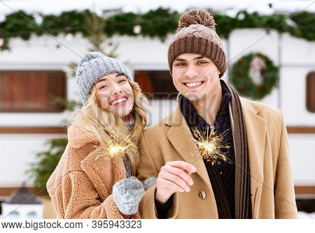 Beautiful Young Couple With Sparklers In Hands Posing At Winter Day Outdoors, Enjoying Spending Chri