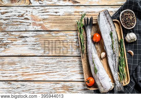 Fresh Pollock Fish. Raw Seafood. White Wooden Background. Top View. Copy Space