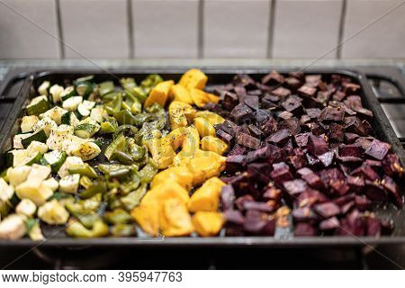 Oven-baked Vegetables On Black Baking Tray. Sliced Baked Green Peperoni, Yellow Sweet Potatoes, Beet