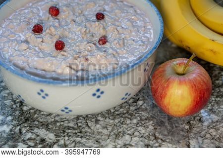 Fresh Yogurt With Cereals And Sliced Fruits, Banana, Apple, Decorated With Little Strawberry From Th