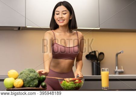 Fit Asian Woman Cooking Salad Slimming And Dieting Standing In Kitchen, Preparing Healthy Vegetable