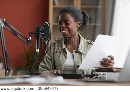 Portrait Of Smiling African-american Woman Singing To Microphone While Recording Music In Home Studi
