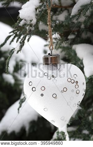 Christmas White Heart Adorns A Coniferous Tree In The Snow
