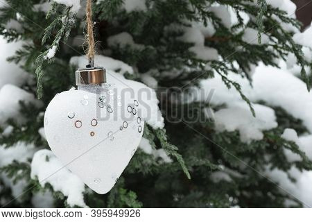 New Years White Heart Adorns A Coniferous Tree In The Snow