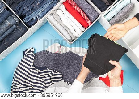 Woman And Kid Hands Folds And Puts Clothes To Baskets. Vertical Storage Of Clothing, Tidying Up, Roo