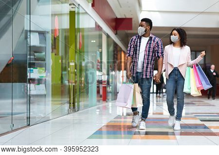 Pandemic Shopping. Black Couple Wearing Protective Face Medical Masks Walking With Shopper Bags In M