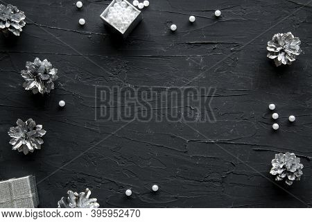Silver Glittering Pinecones On Black Background. Christmas Decoration And Pine Cones, Top View. Spac