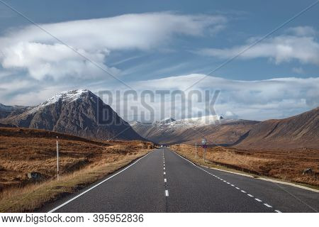 Road Leading Through The Scottish Highlands Of Glen Coe, Snowcapped Mountains And Valley. Scotland,