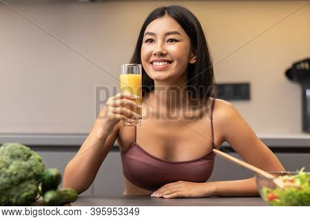 Detox Diet And Weight Loss. Slim Korean Woman Drinking Juice In Kitchen, Eating Healthy Vegetable Sa
