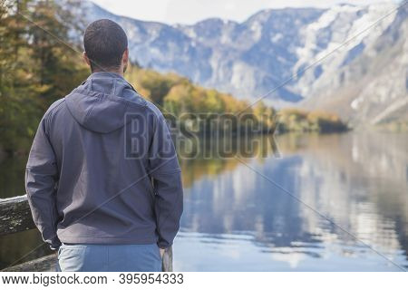 A Man Stands Near Lake Bohinj In Slovenia With His Back Turned