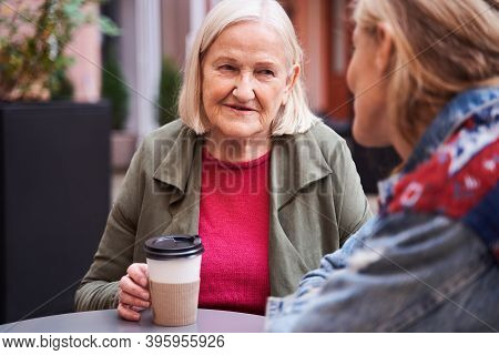 Woman Drinking Coffee At The Street Cafe