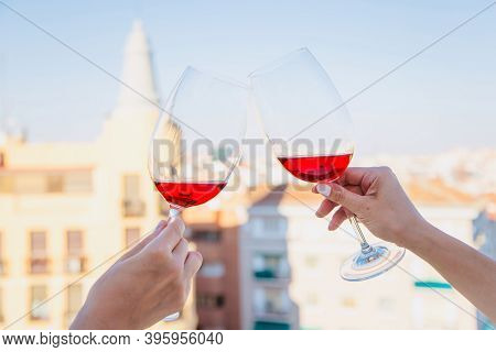 Two Female Hands With Glasses Of Wine Clink Glasses Against The Background Of City Buildings. Two Gl