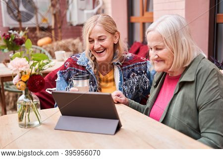 Woman And Her Adult Daughter Looking At The Digital Tablet