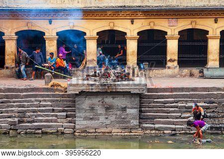 Kathmandu, Nepal - April 15, 2012: Hindu Cremation Ritual At The Bagmati River Ghats Near The Pashup