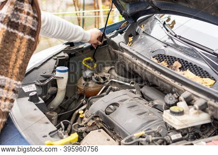 The Girl Is Looking For A Breakdown On The Hood Of The Car, Checks The Oil. Close-up.