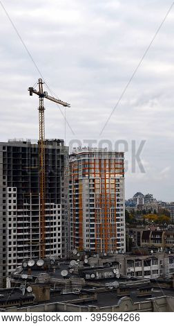 Construction Site Of Unfinished Multistory Building With Crane Jib Moving With Overcast Sky Backgrou