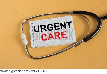 Notepad With Text Urgent Care Lies With A Stethoscope On An Orange Background