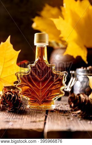 A Bottle Of Delicious Maple Syrup With Maple Leaves On Wooden Forest Background