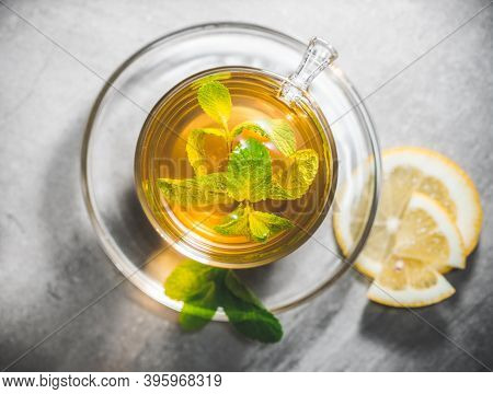 Glass Cup Of Mint Tea Leaves With Fresh Slice Lemon On Gray Table. Topview, Above.