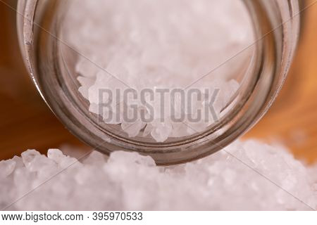 White Sea Salt Pours Out Of The Jar. Sea Salt Crystals. Large Crystals Of Sea Salt Close-up.