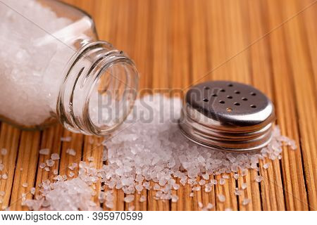 Scattered Crystals Of White Salt From A Salt Cellar. White Sea Salt Pours Out Of The Jar.